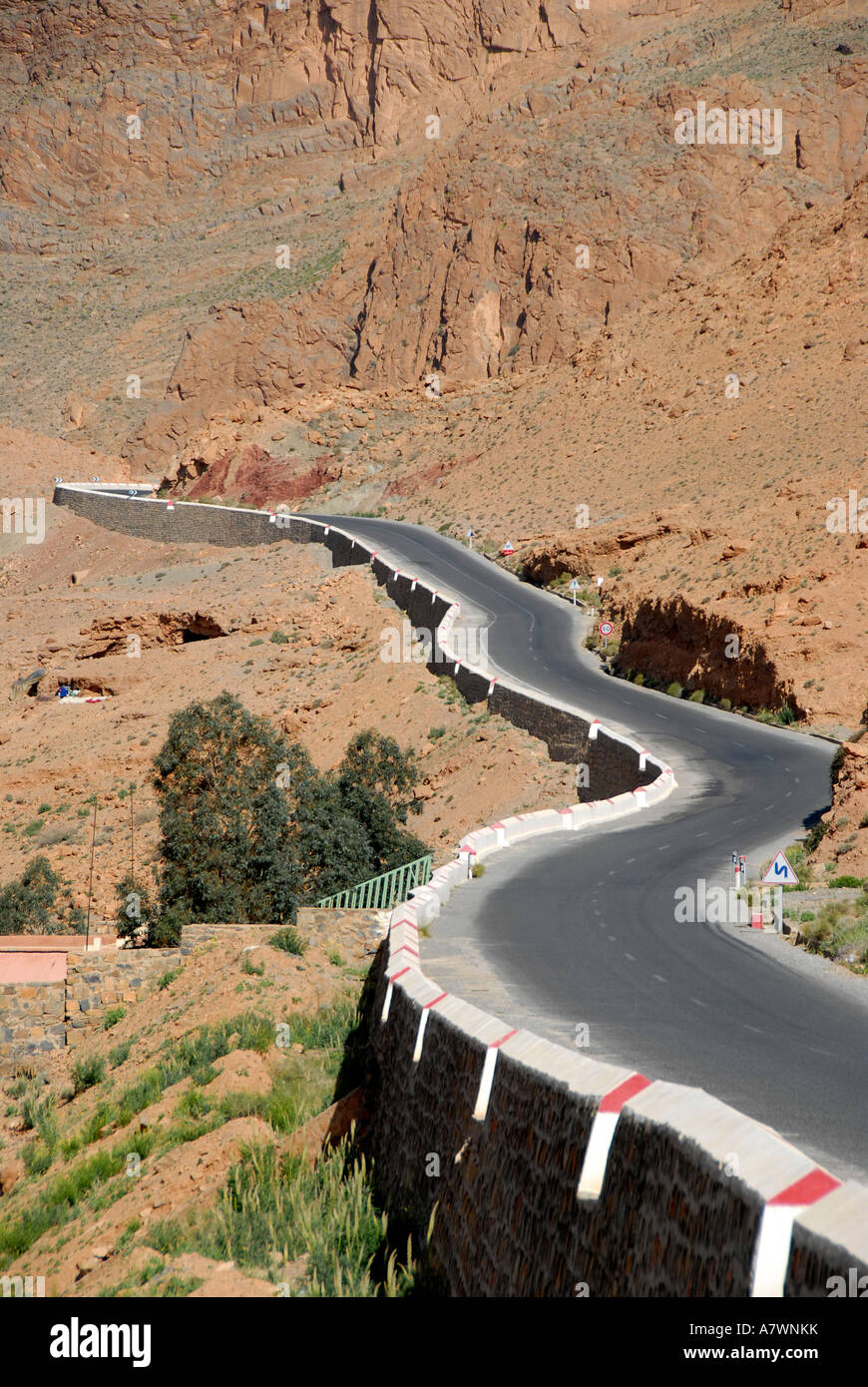 Country road winds through red rock mountains High Atlas Gorges du Zis near Ar-Rachidia Morocco - Stock Image