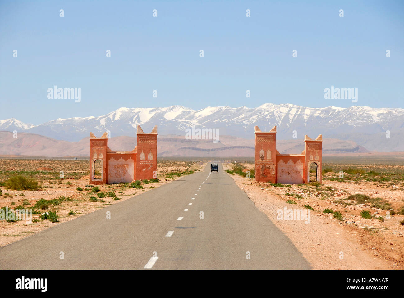 Car drives on straight street through a gate towards snowcapped mountains of the High Atlas between Tinerhir and Stock Photo