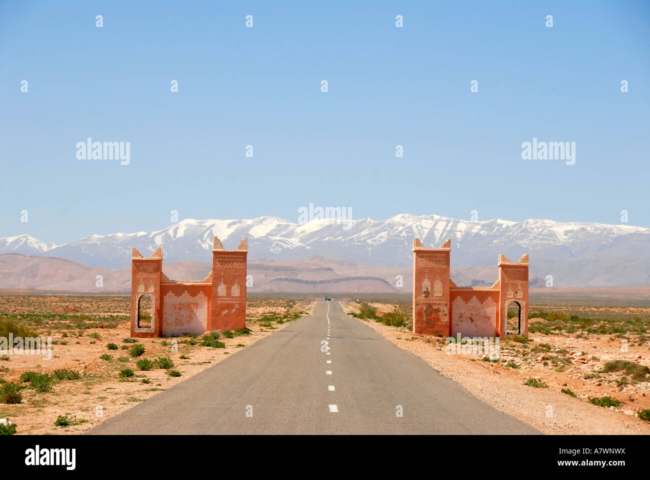 Straight street runs through a gate towards snowcapped mountains of the High Atlas between Tinerhir and Boumalne Stock Photo