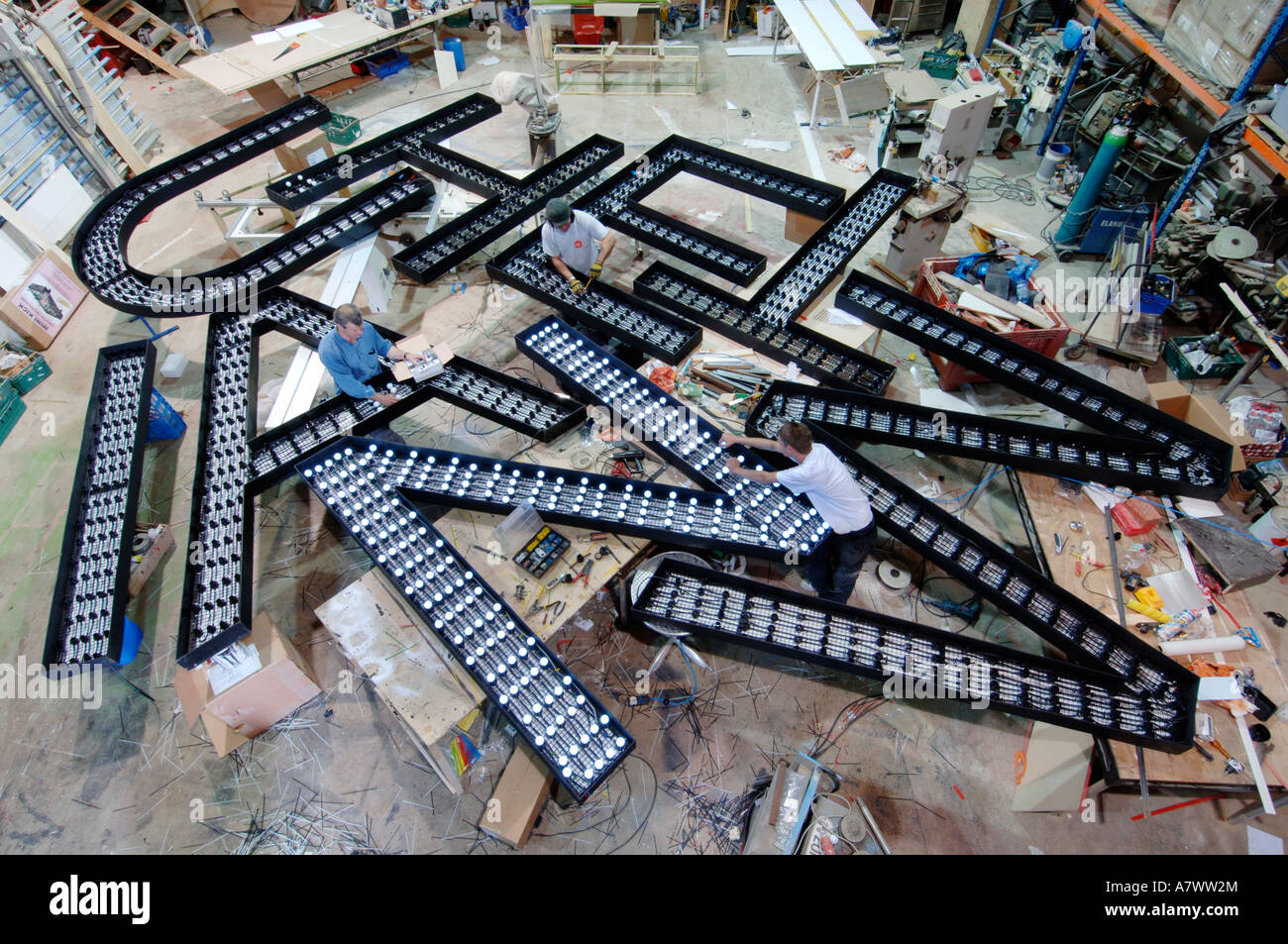 Giant cut outs of capital letters being fitted with lights by electricians - Stock Image