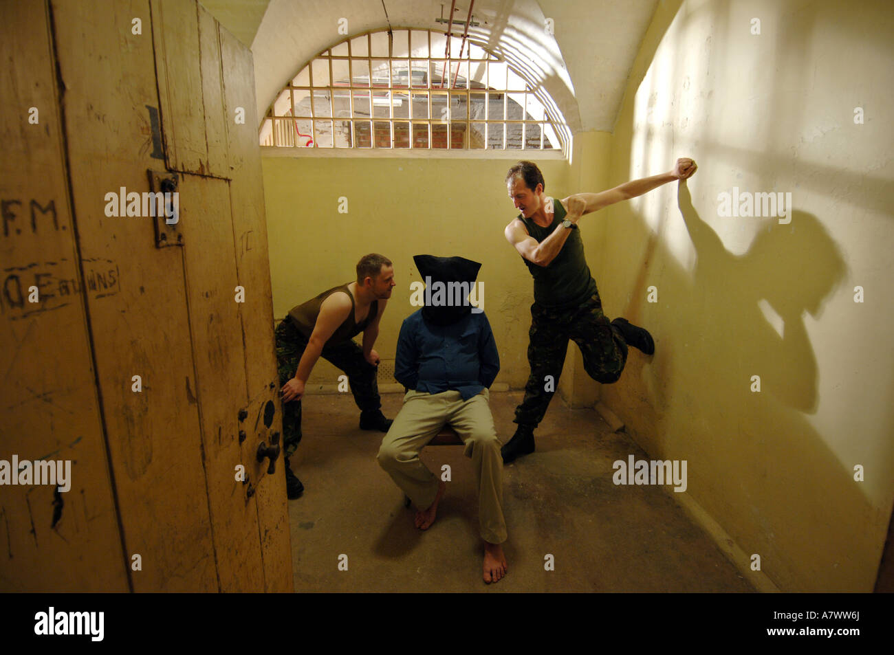 Two thugs question a hooded prisoner in a scene from a Pinter play - Stock Image