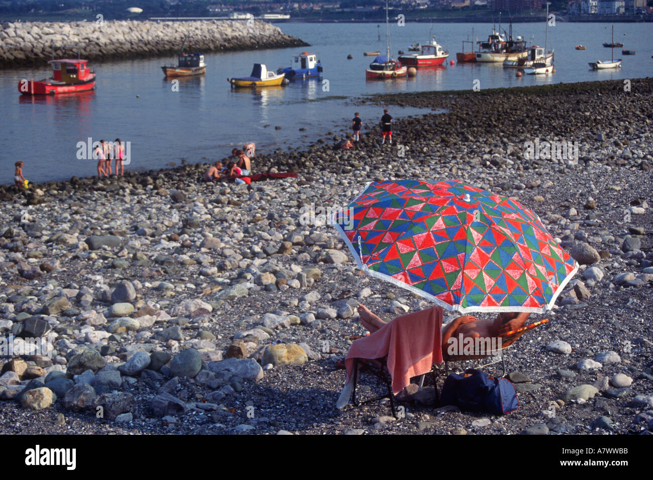 Boats and People on Beach Rhos on Sea Conwy North West Wales - Stock Image