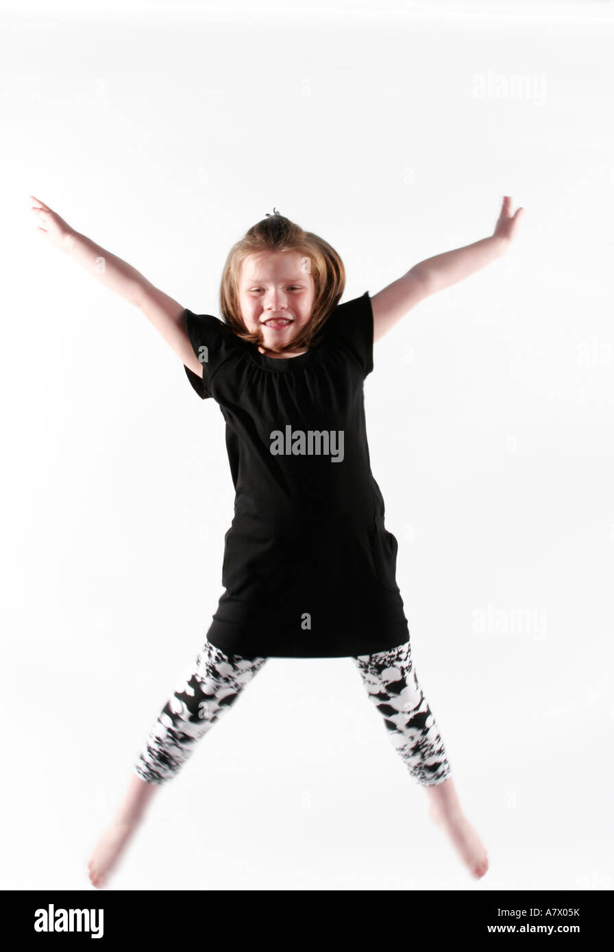 Girl does a star jump, captured mid air - Stock Image