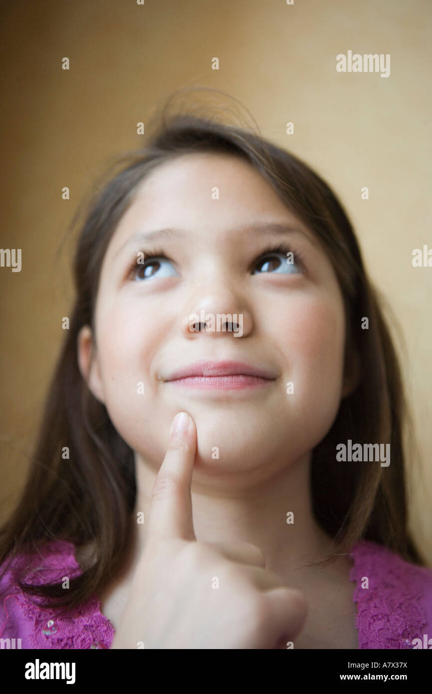 close up of eight year old hispanic girl trying to remember something - Stock Image