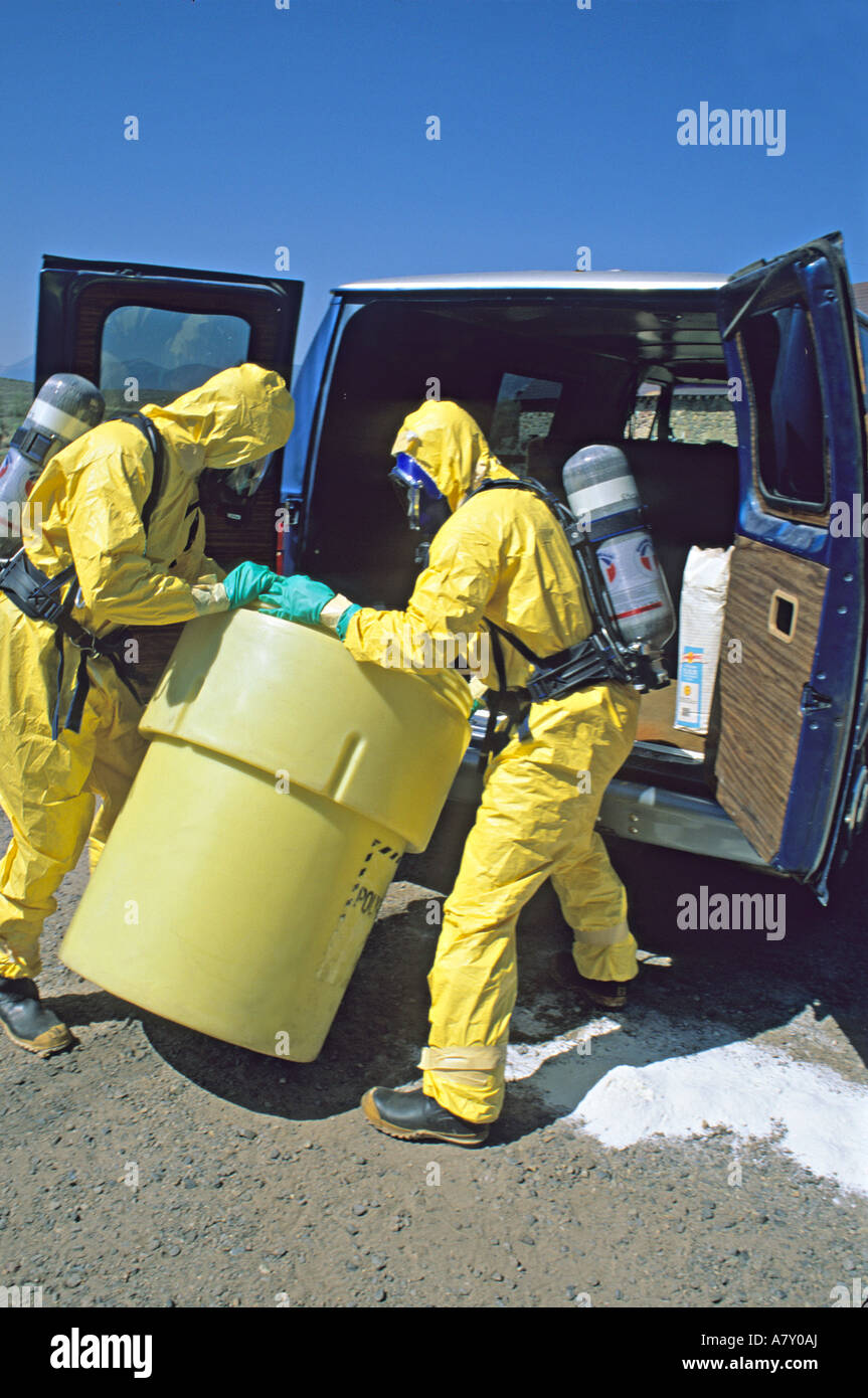Hazmat team places steel drum into plastic safety container. - Stock Image