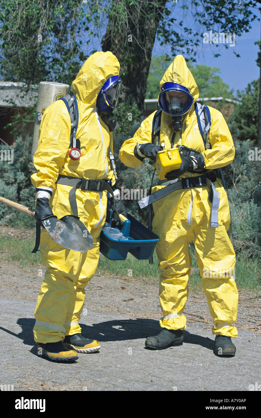 Hazmat team prepares to approach toxic substance spill. - Stock Image
