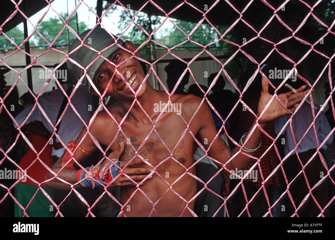 Local tattooed character behind mesh screen Taungboyone August Nat Festival nr Mandalay Burma - Stock Image