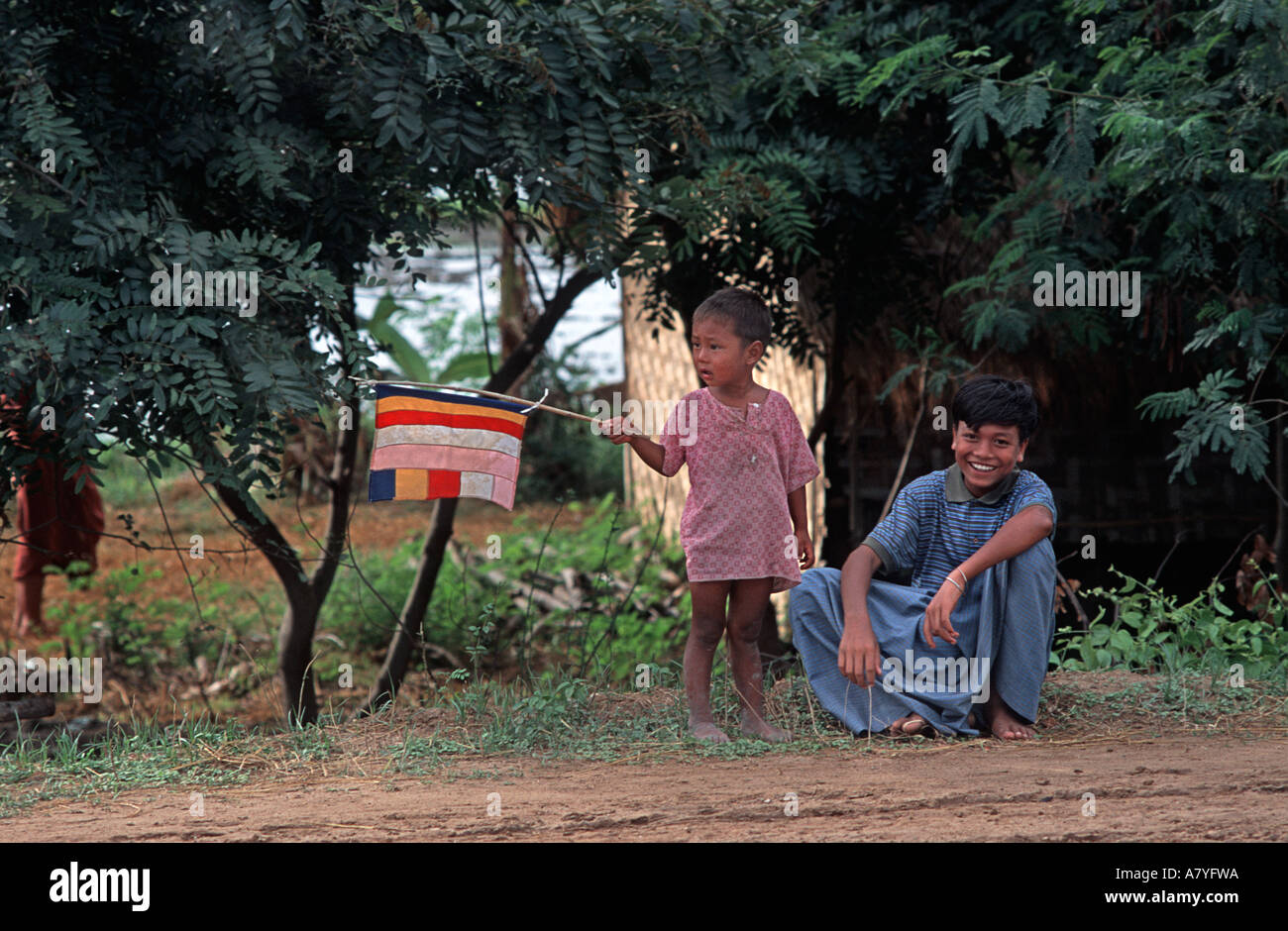 Burmese children on the road from Mandalay to Taungboyone Flag waving youngster Nat Festival Burma MYANMAR - Stock Image