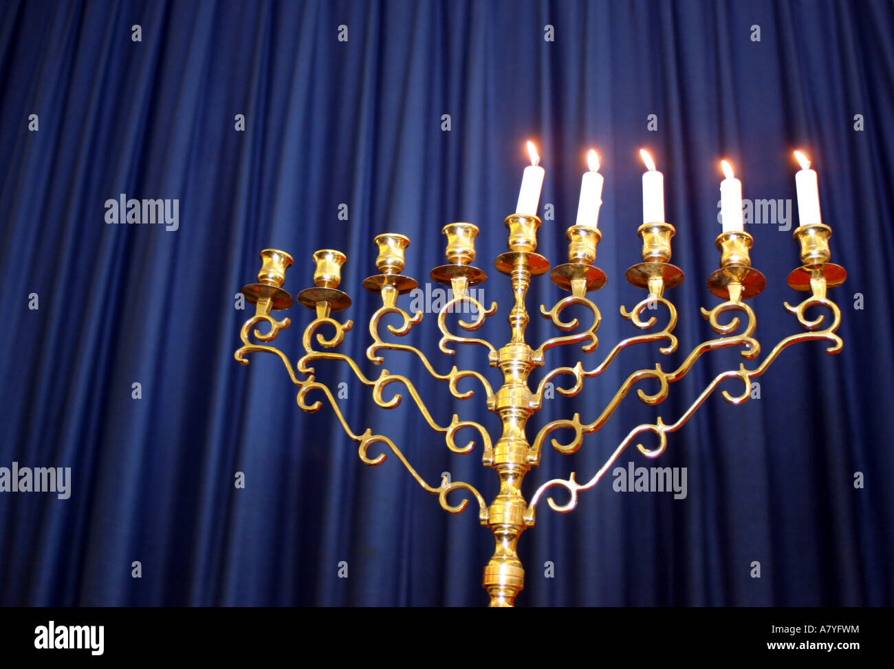 Partially lit Hanukkah menorah against a blue curtain backdrop - Stock Image