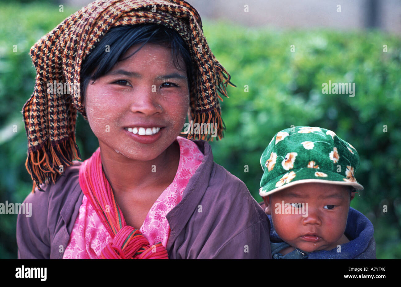 Friendly mother carrrying child at Kalaw market near Inle Burma MYANMAR - Stock Image