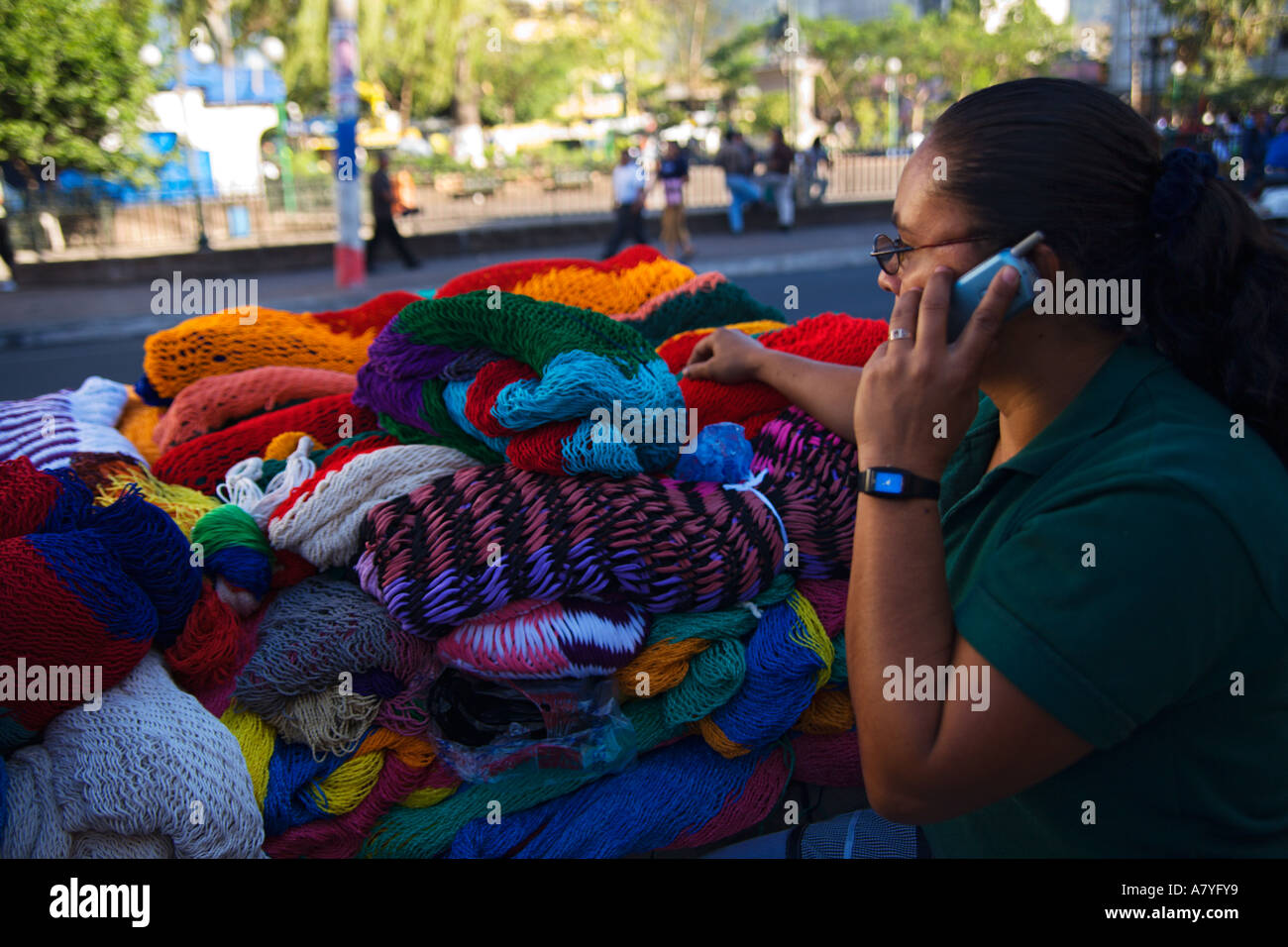 Lady street vendor on mobile phone whilst selling her knit-wear in San Salvador city Republic of El Salvador Central America - Stock Image