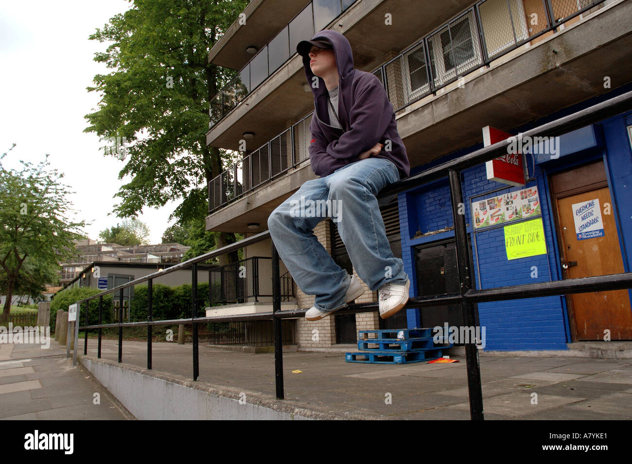 Young boy hanging around the streets dressed in hoodie looking threatening and bored. - Stock Image
