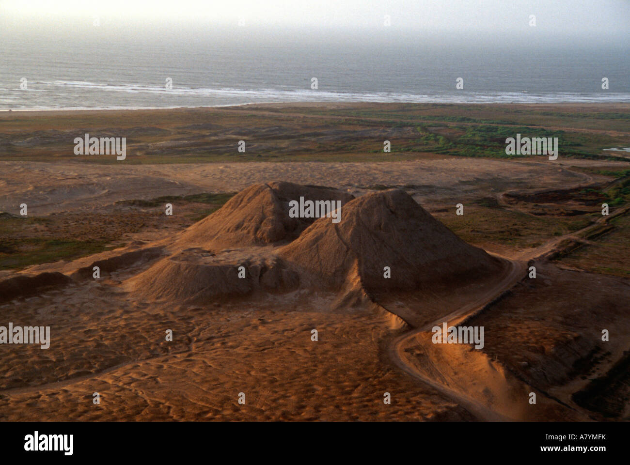 Aerial view of Huaca Dos Cabezas, corner of mudbrick pyramid, was looted by the Spanish, Pacific ocean on the horizon - Stock Image