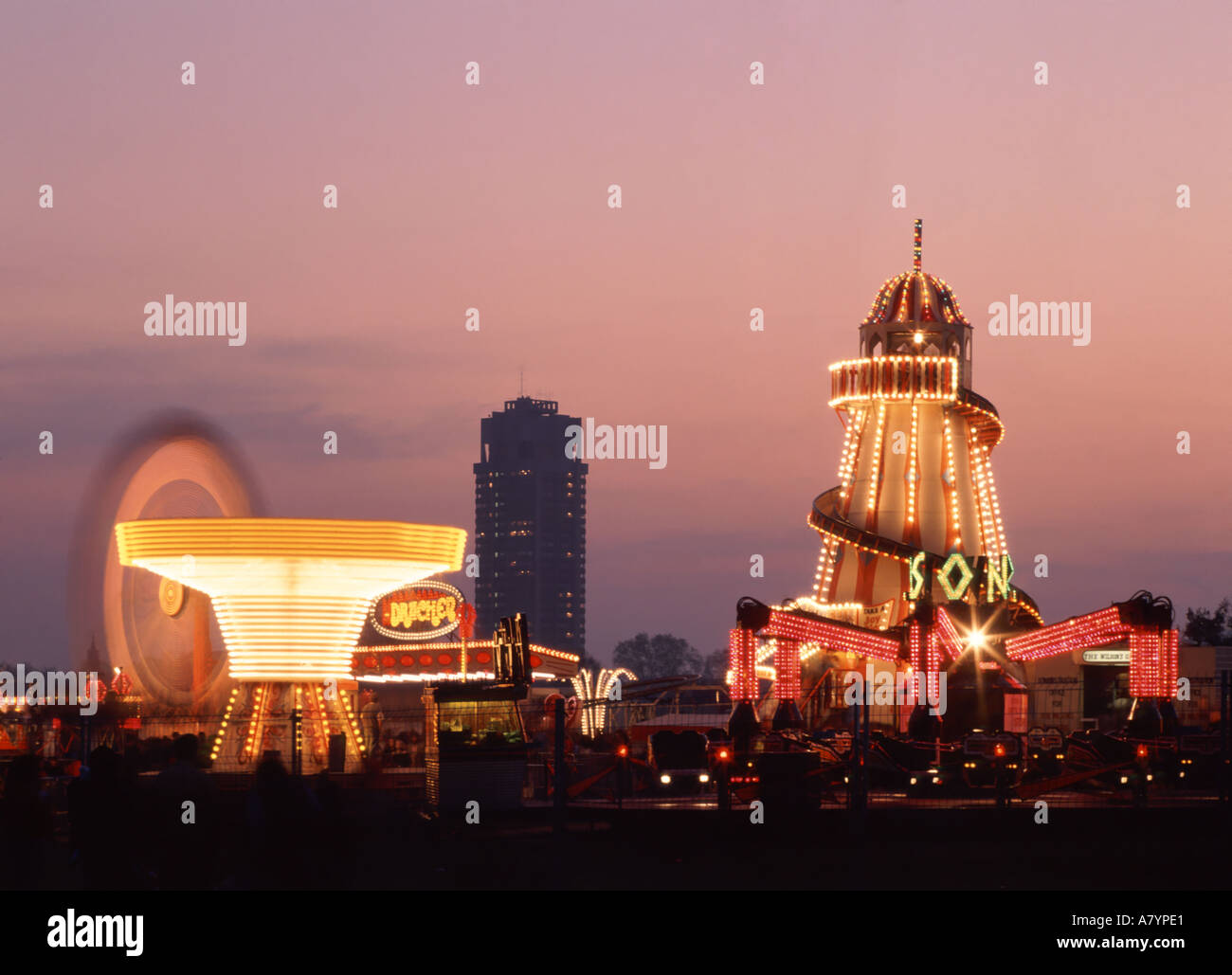 London Hyde Park special event fairground at dusk with tower block of Knightsbridge Army barracks distant Stock Photo
