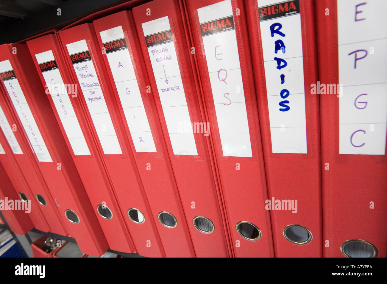 Red files identified in Spanish language in a row on an office shelf - Stock Image