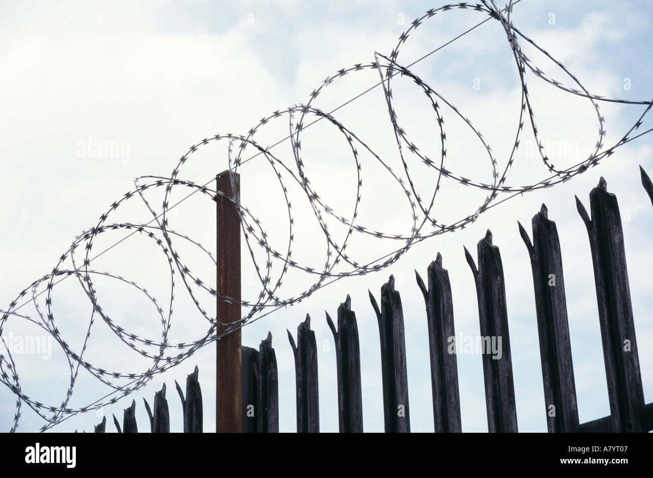 England coiled razor wire placed on top of spiked metal security ...