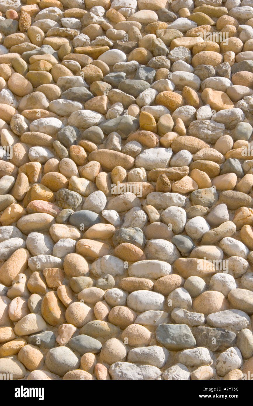 Pattern created by cemented pebbles used as facing on wall - Stock Image