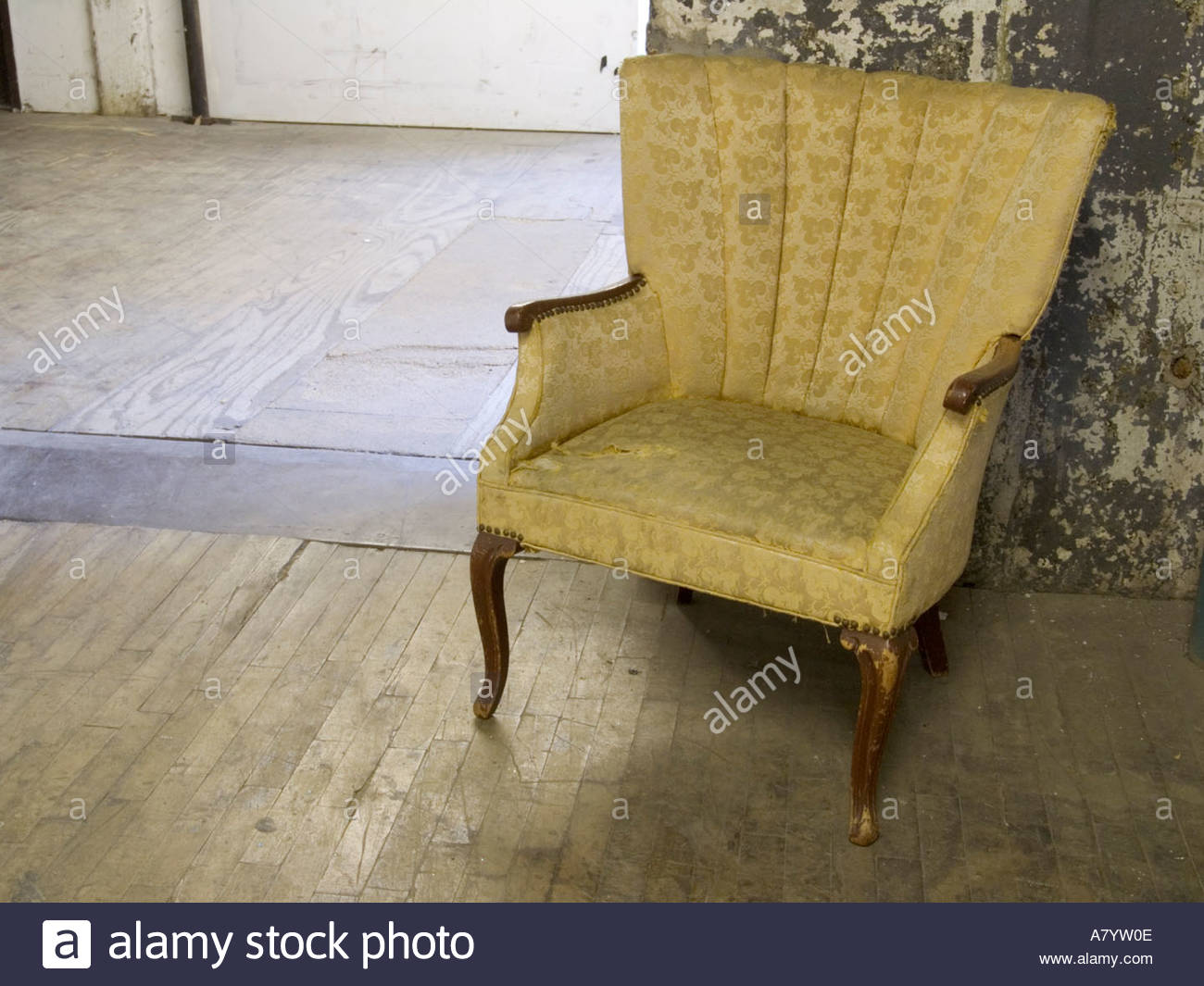 an old arm chair in the hallway of an old industrial building - Stock Image