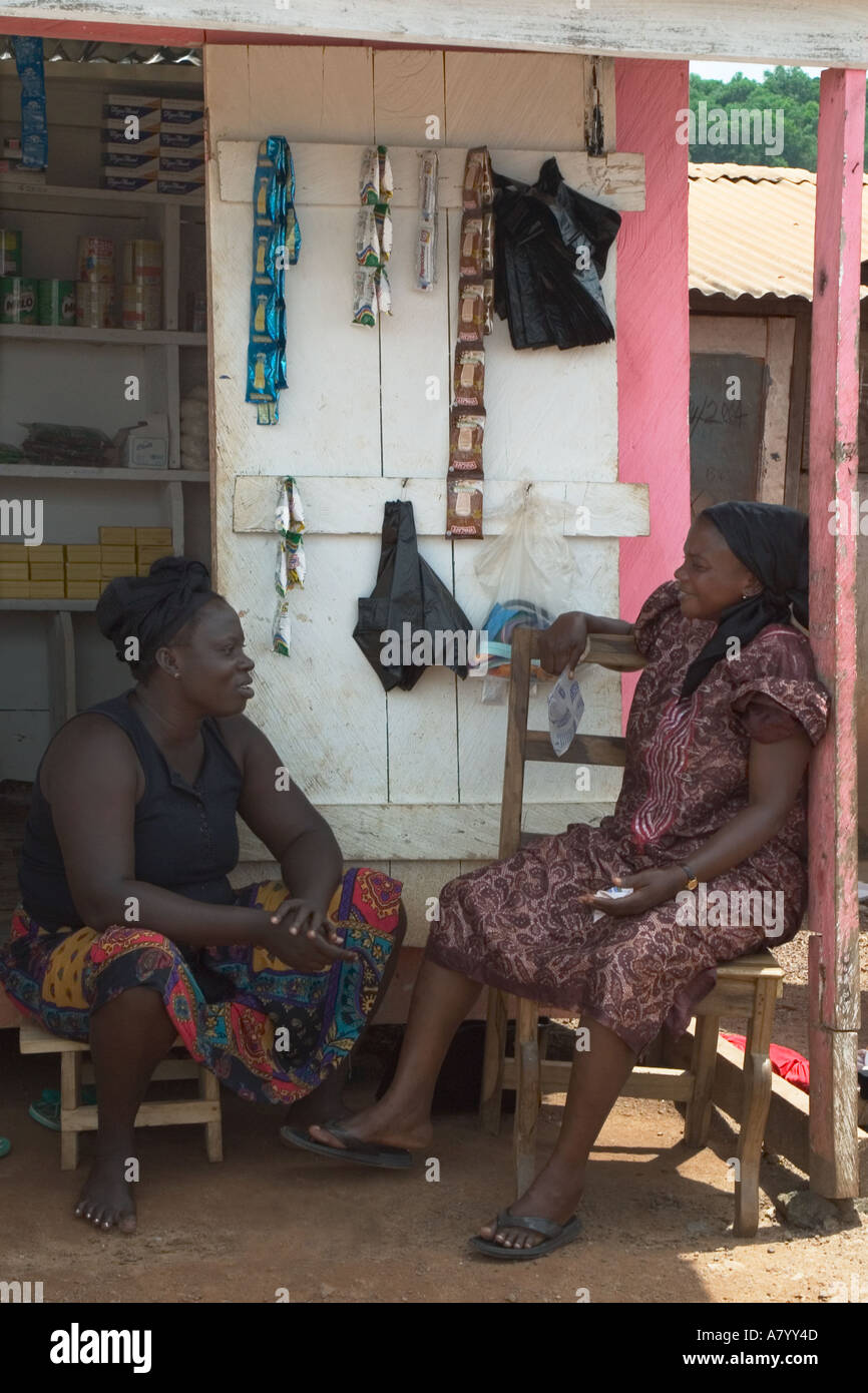 Two West African women market traders chatting outside their grocery stall Ghana West Africa Stock Photo