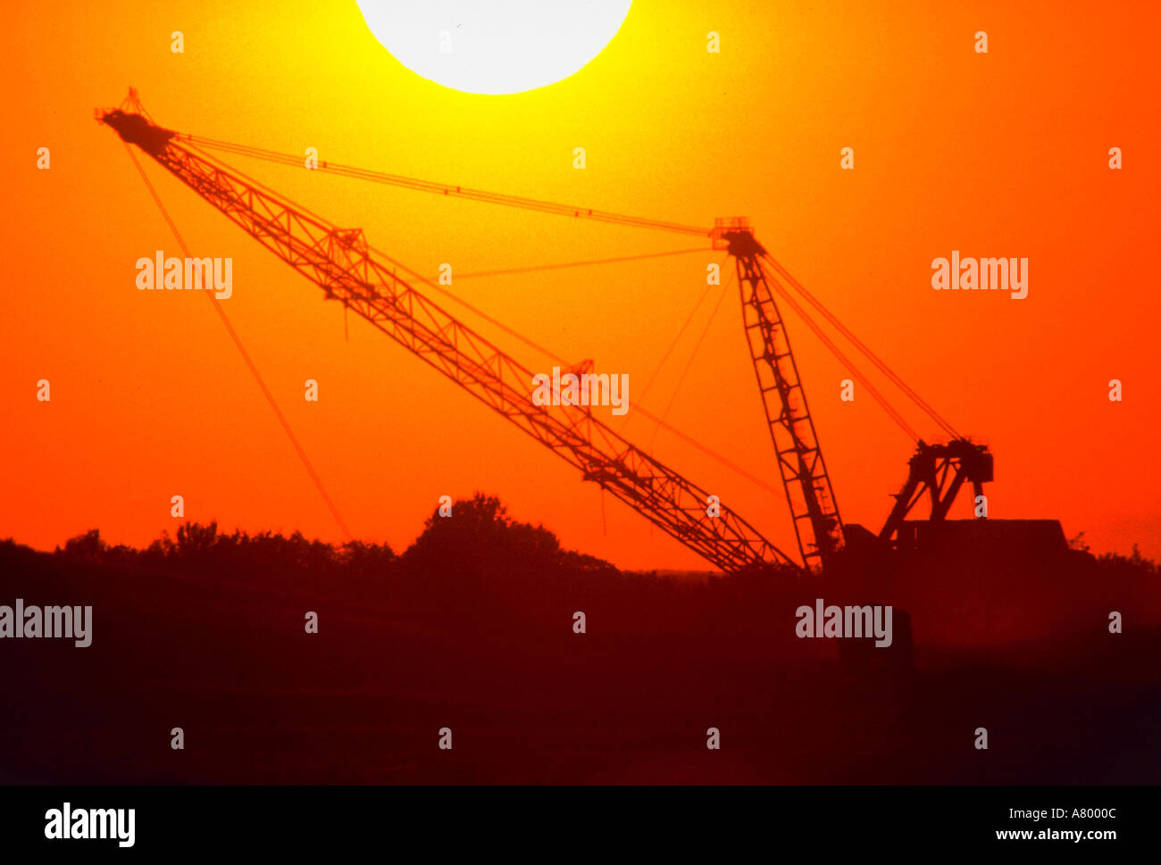 Sunset silhouette of giant dragline at Texas coal strip mine - Stock Image