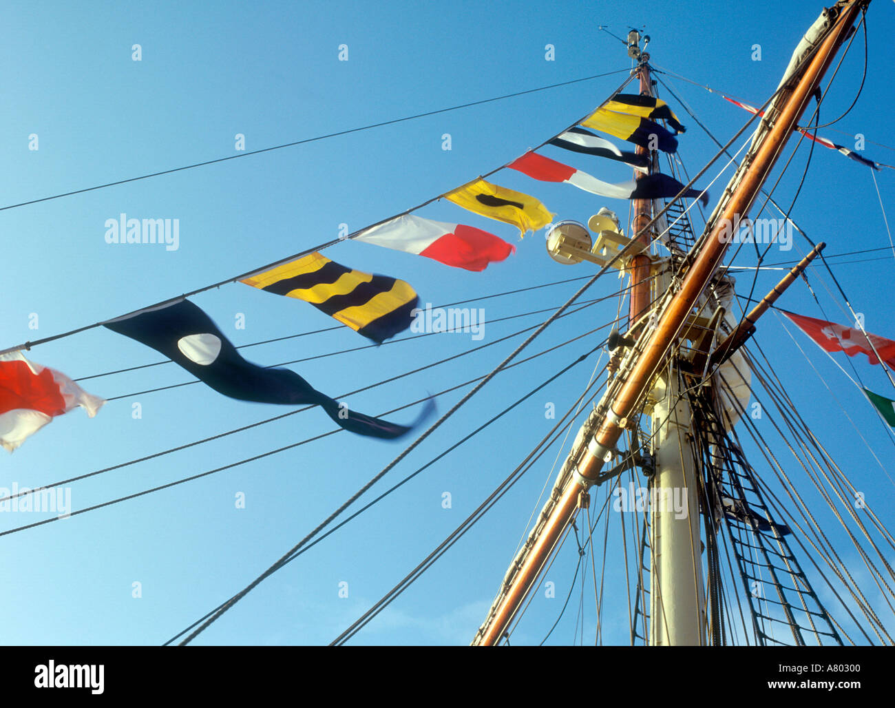 Coloured flags on the mast of a tall ship Stock Photo
