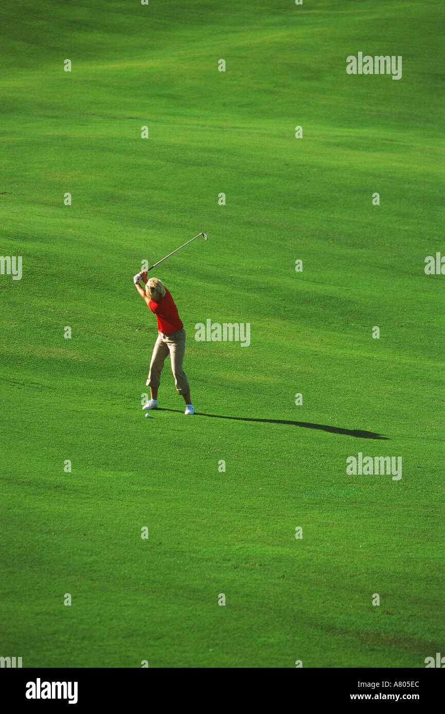 Woman with perfect form hitting iron shot off lush green fairway - Stock Image