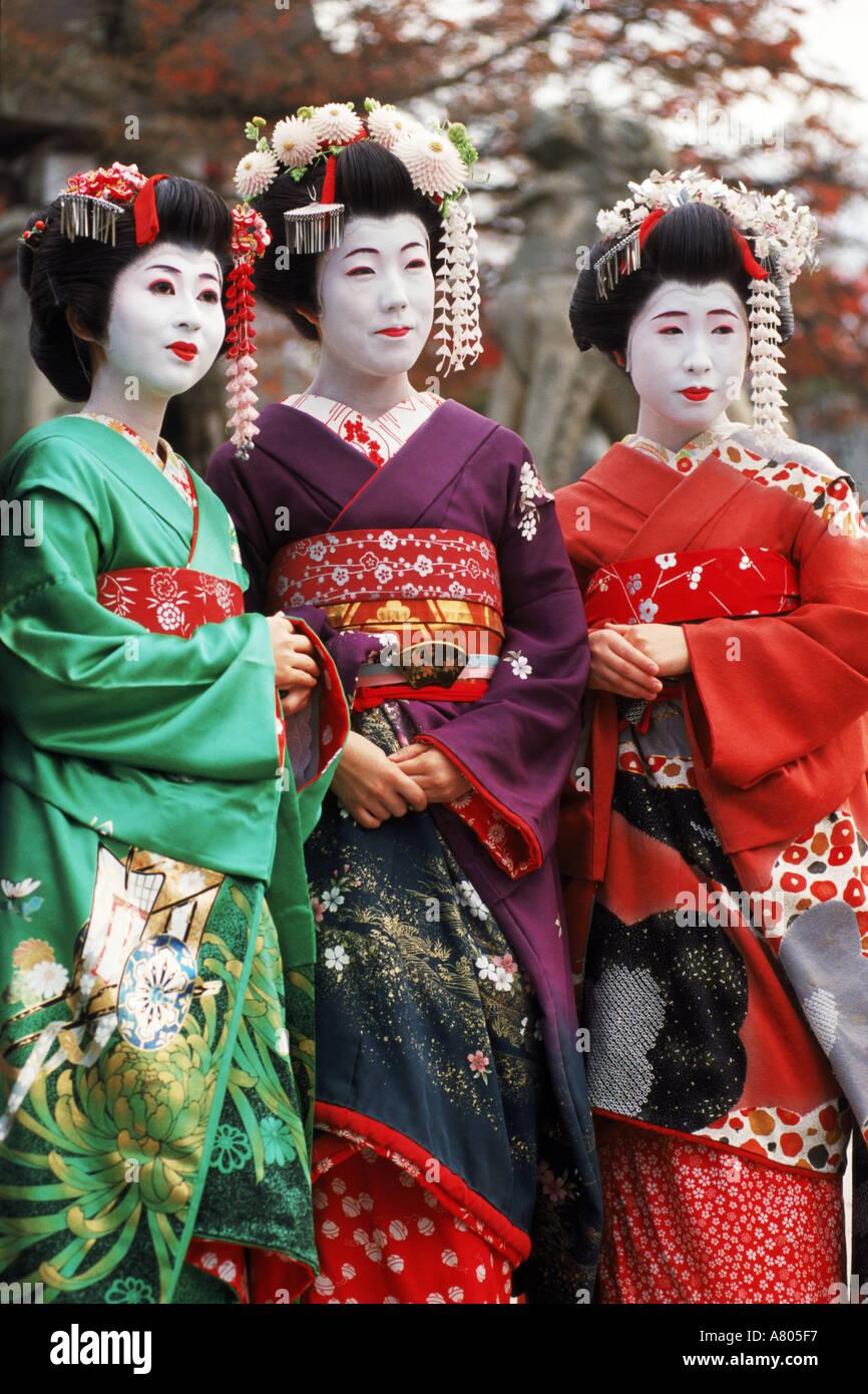 Three Geishas in colorful kimonos at shrine in Kyoto - Stock Image