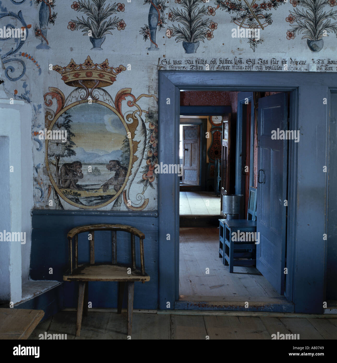Wall paintings and mural beside doorway with blue frame in rustic ...