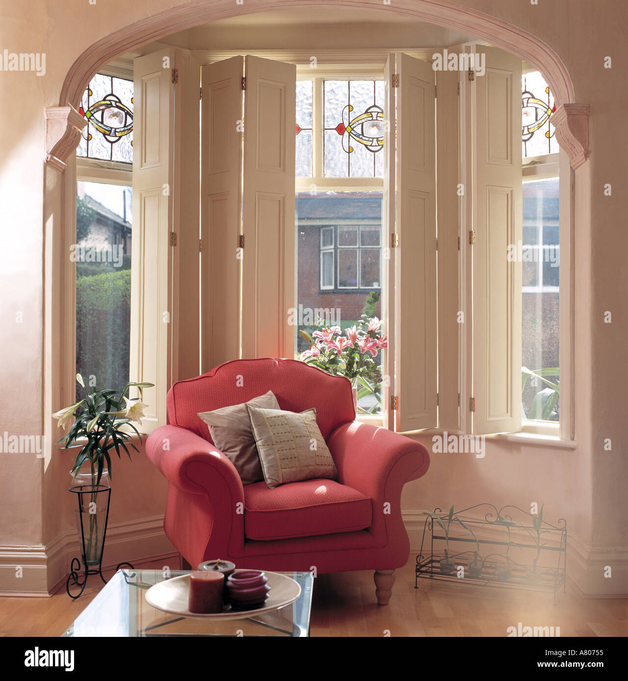Pink Armchair In Bay Window With White Shutters And Stained