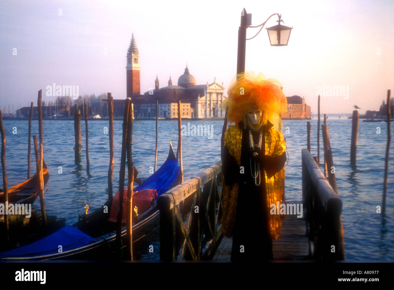 Carnival goer in elaborate mask posing on the lagoon Venice Italy - Stock Image