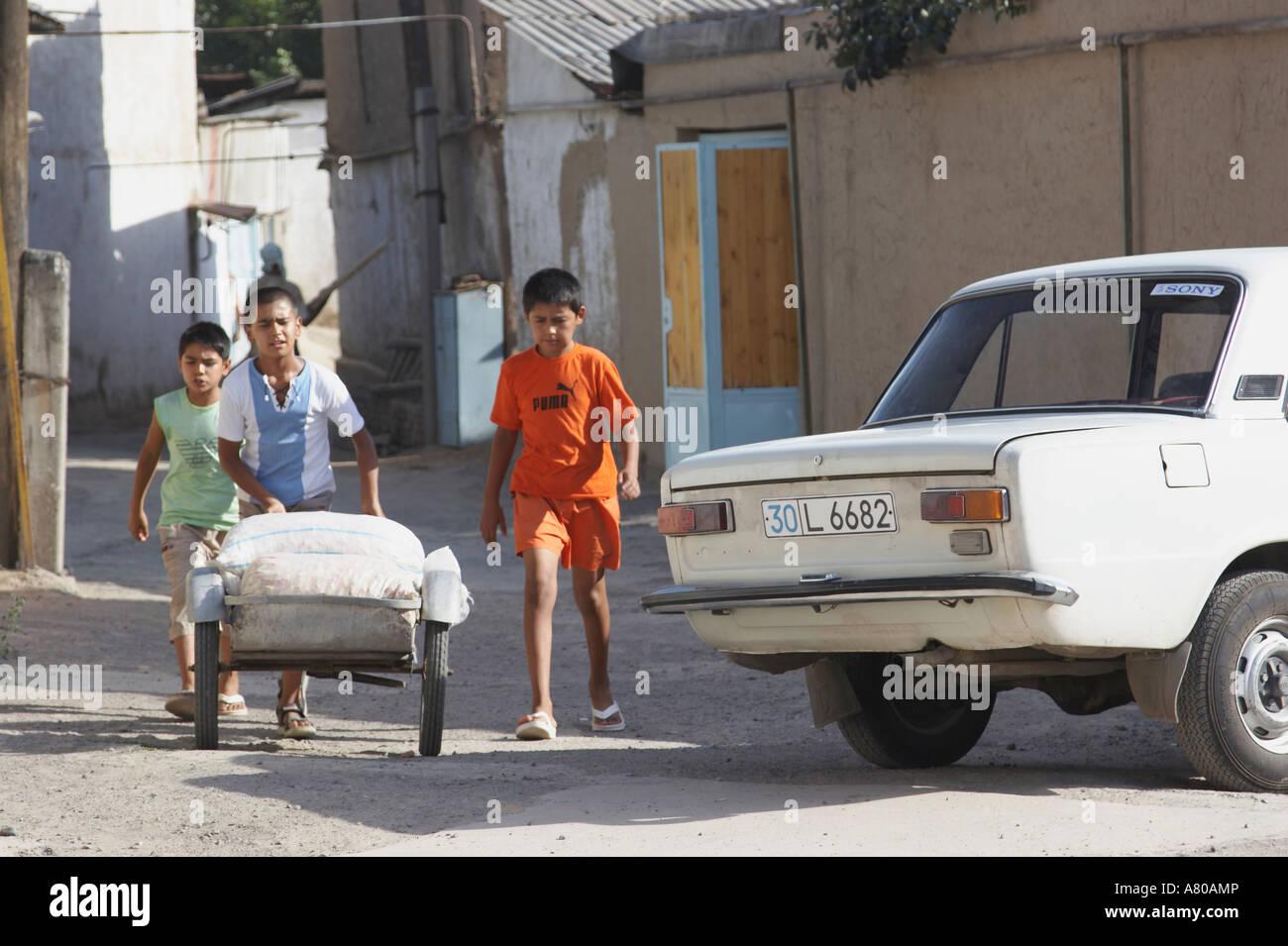Boys Pushing Cart Through Streets Of Chorsu Stock Photo
