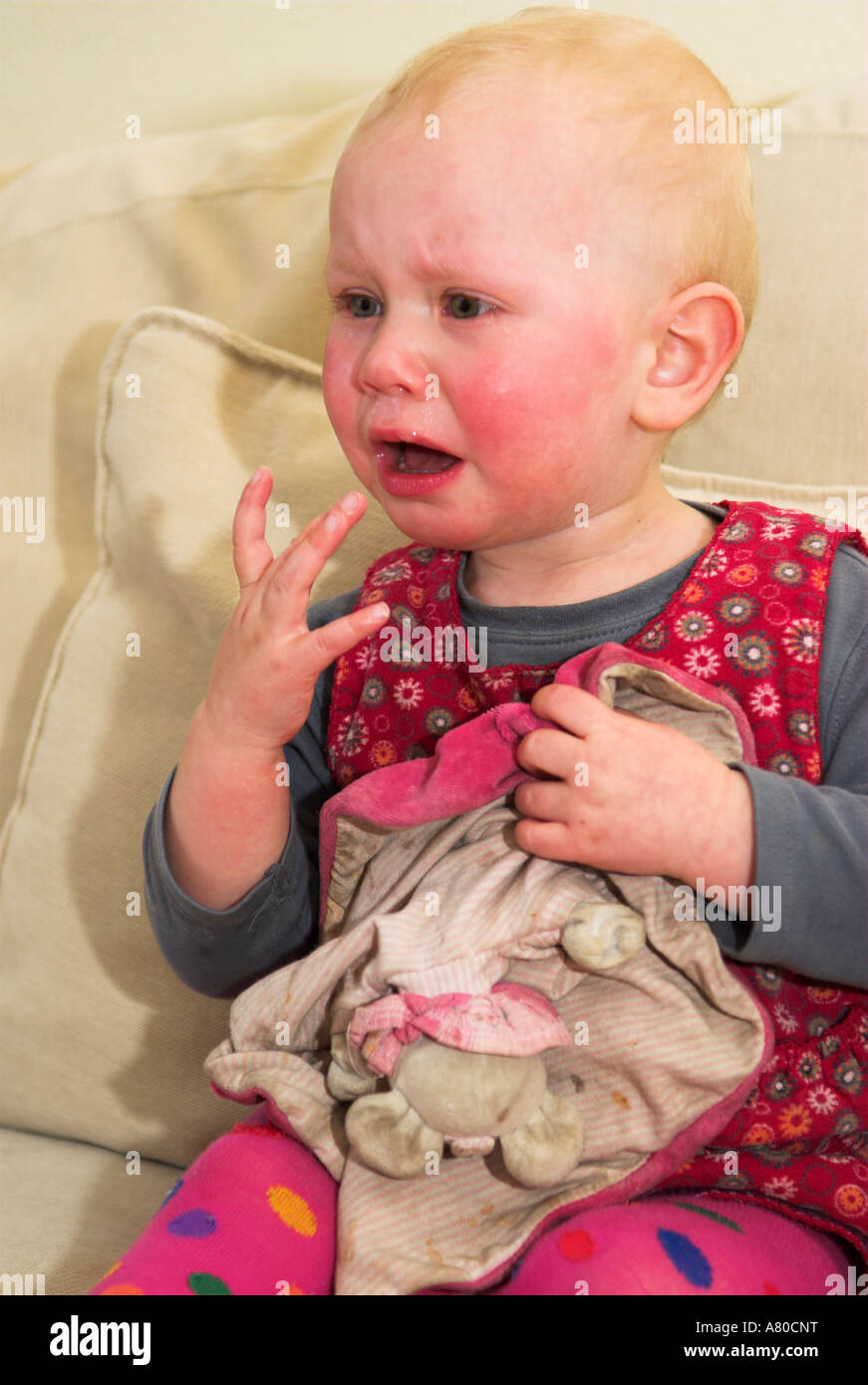 Young little girl on sofa crying - Stock Image