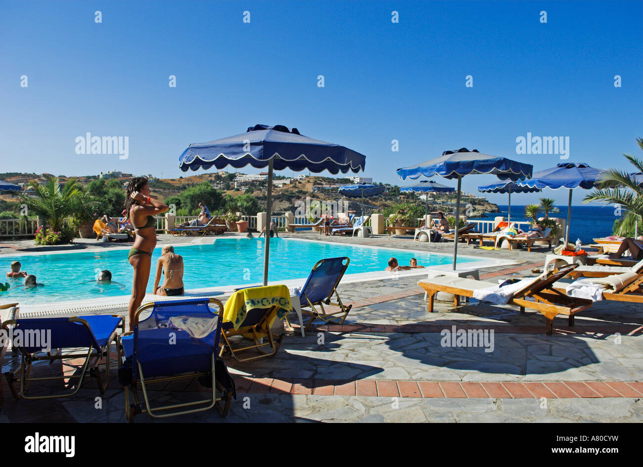 Hotel pool with people  People at hotel pool overlooking sea and hills at Capsis Hotel Aghia ...