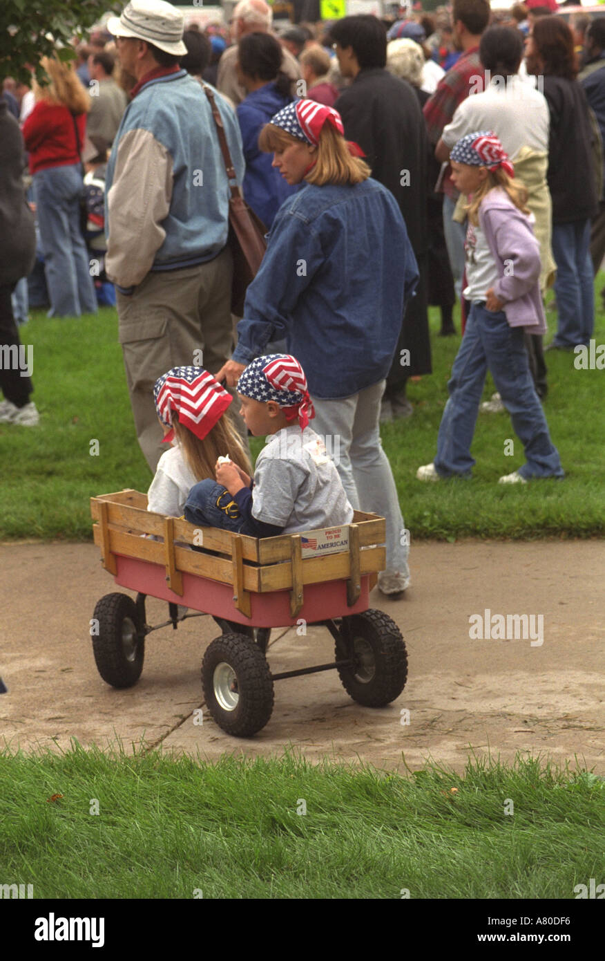 Mom pulling wagon children with flag kerchief at Minnesota Memorial for 9/11 victims at state capitol. St Paul Minnesota MN USA - Stock Image