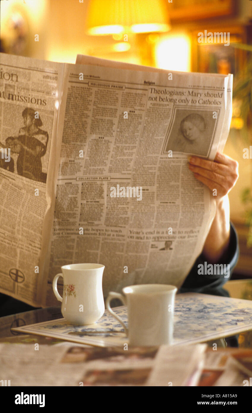 Retired woman starting off her day by reading a newspaper religion section and drinking coffee at  the kitchen table - Stock Image