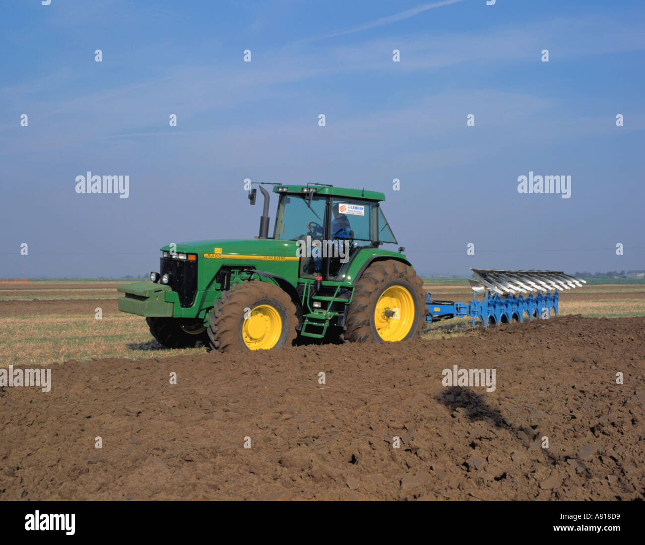 John Deere 8400 tractor with eight furrow reversible plough (State of the art tractor of traditional design). - Stock Image
