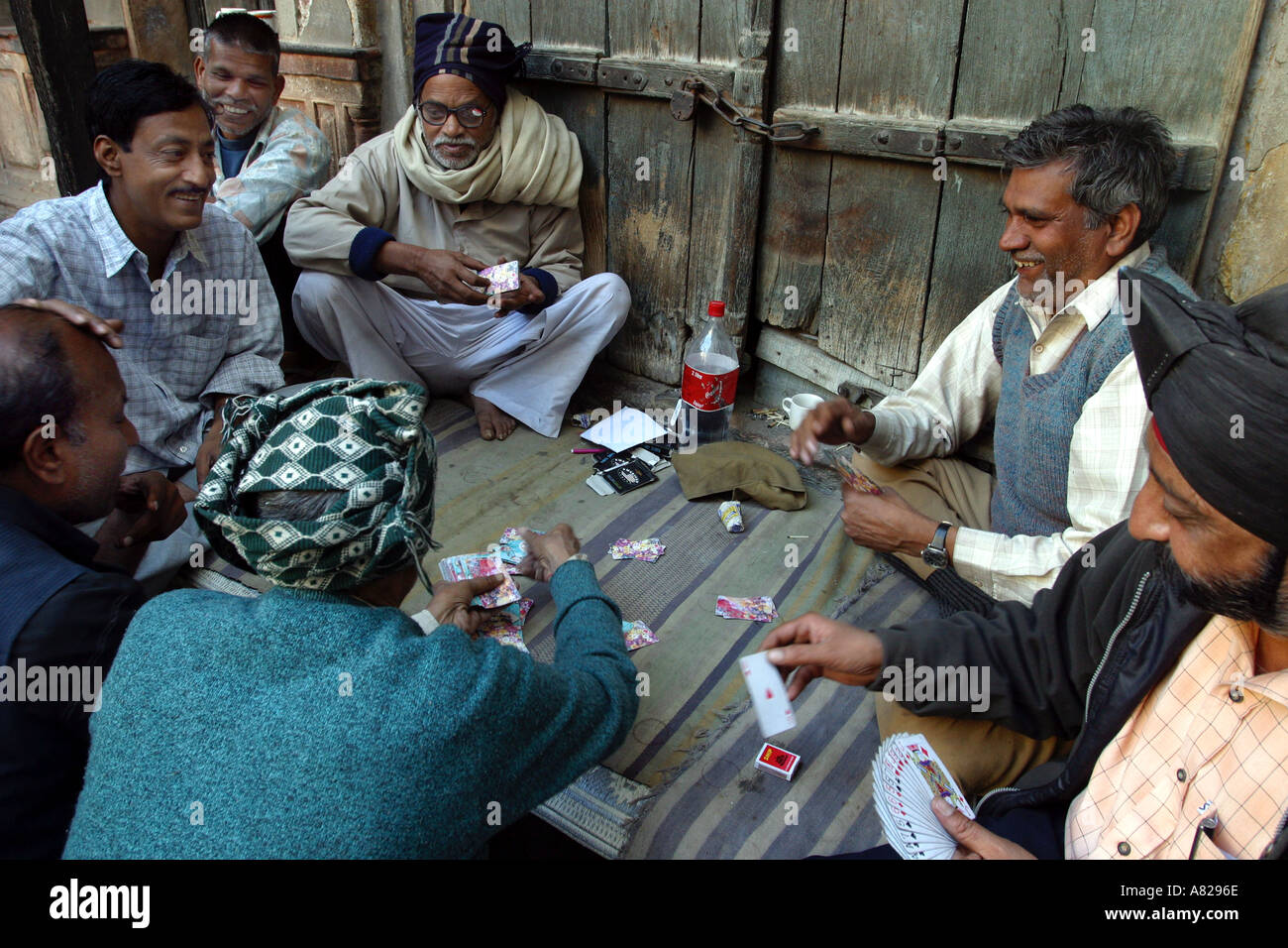 A group of Indian men play cards on the street in Delhi India - Stock Image