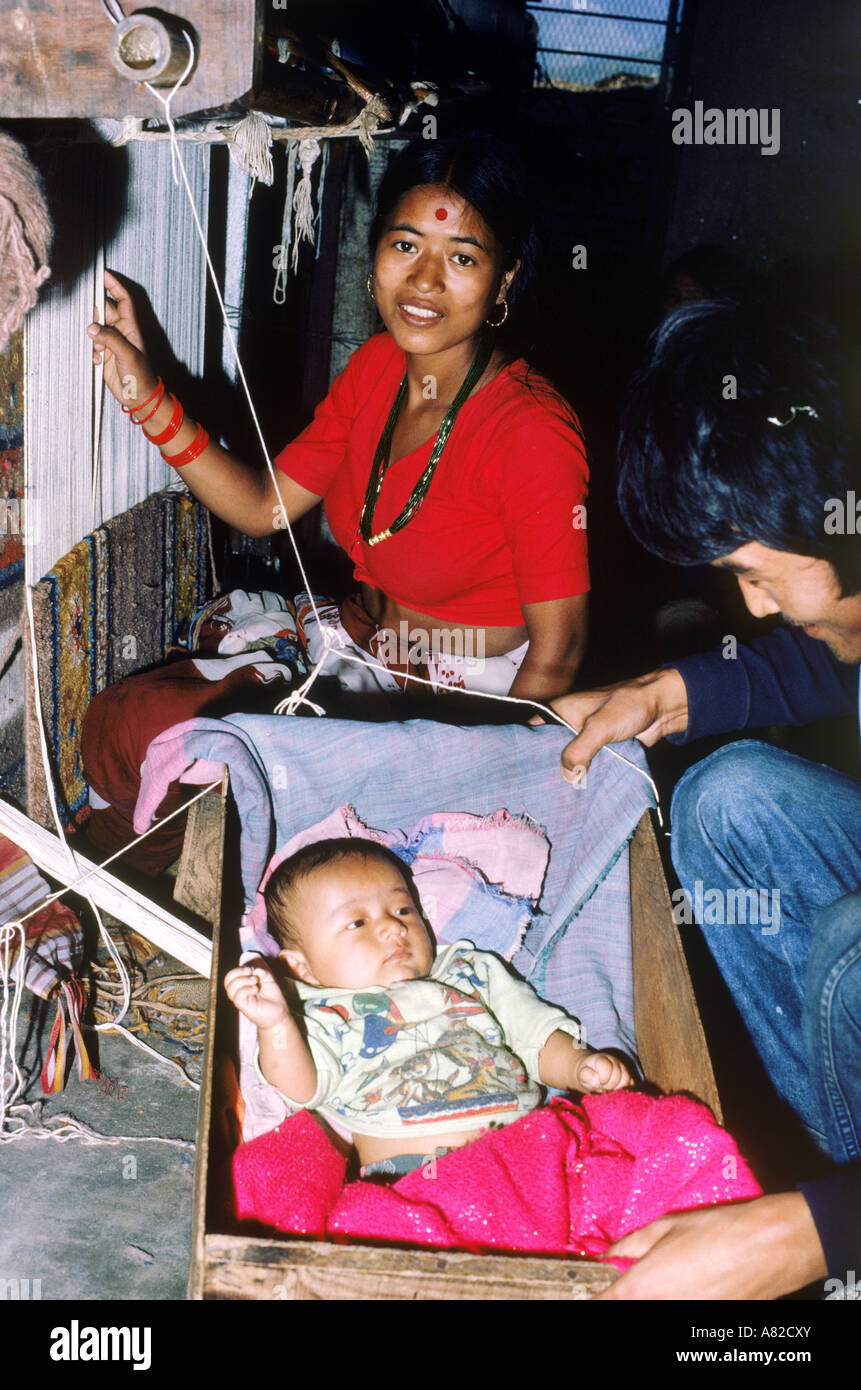 Napalese woman in weaving factory near Katmandu working with loom  while caring for her baby in wooden rocker - Stock Image