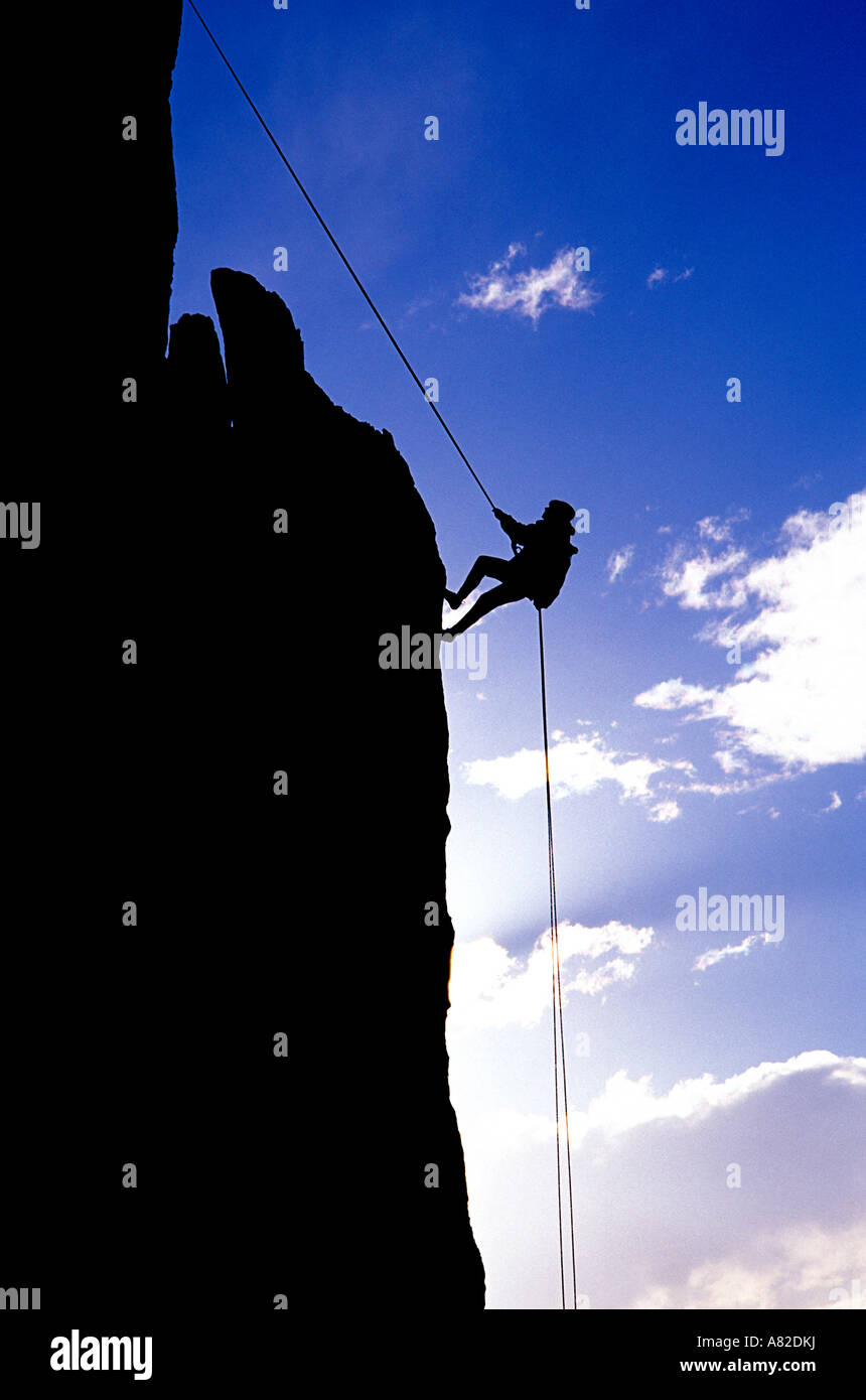 Silhouetted climber rappelling from the summit of Eichorn Pinnacle Yosemite National Park Sierra Nevada Mountains - Stock Image