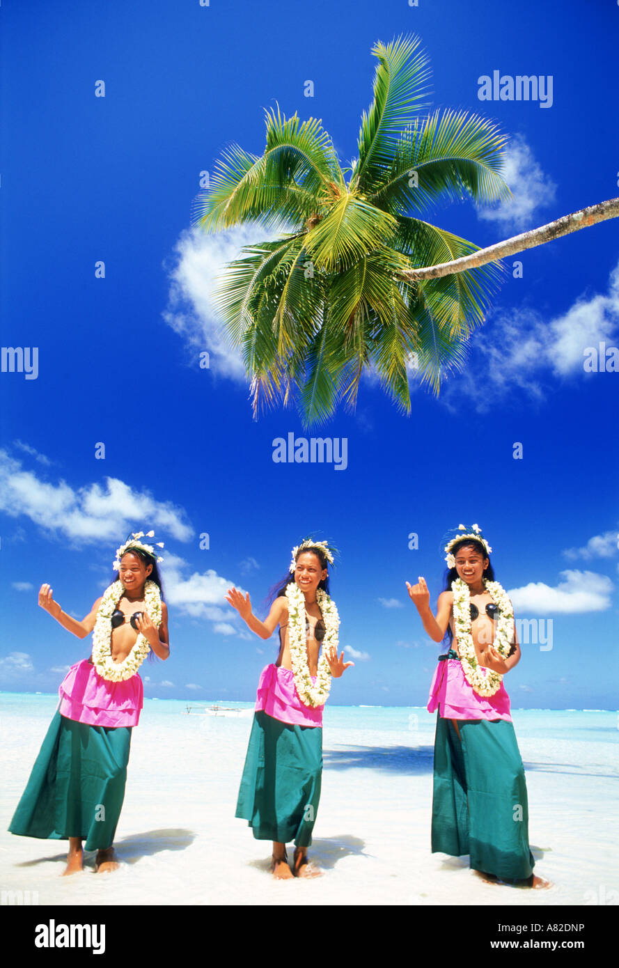 Three Polynesian girls with grass skirts and flower leis on Aitutaki Island in South Pacific - Stock Image