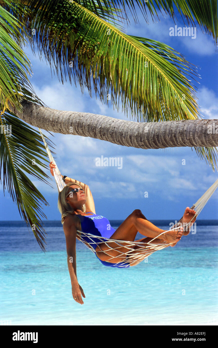 Woman with sunglasses relaxing in hammock under palm tree - Stock Image