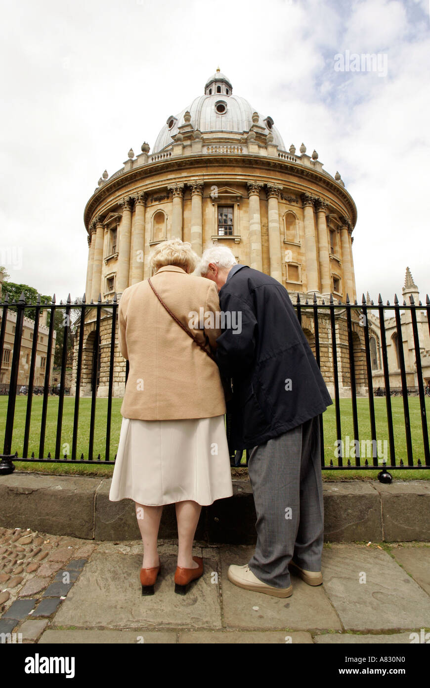 two elderly sightseers in Oxford in front of Radcliffe Camera - Stock Image