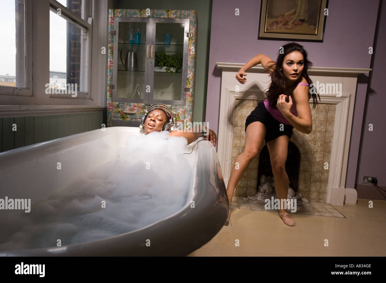 Two young women in the bathroom, one immersed in the bathtub with ...