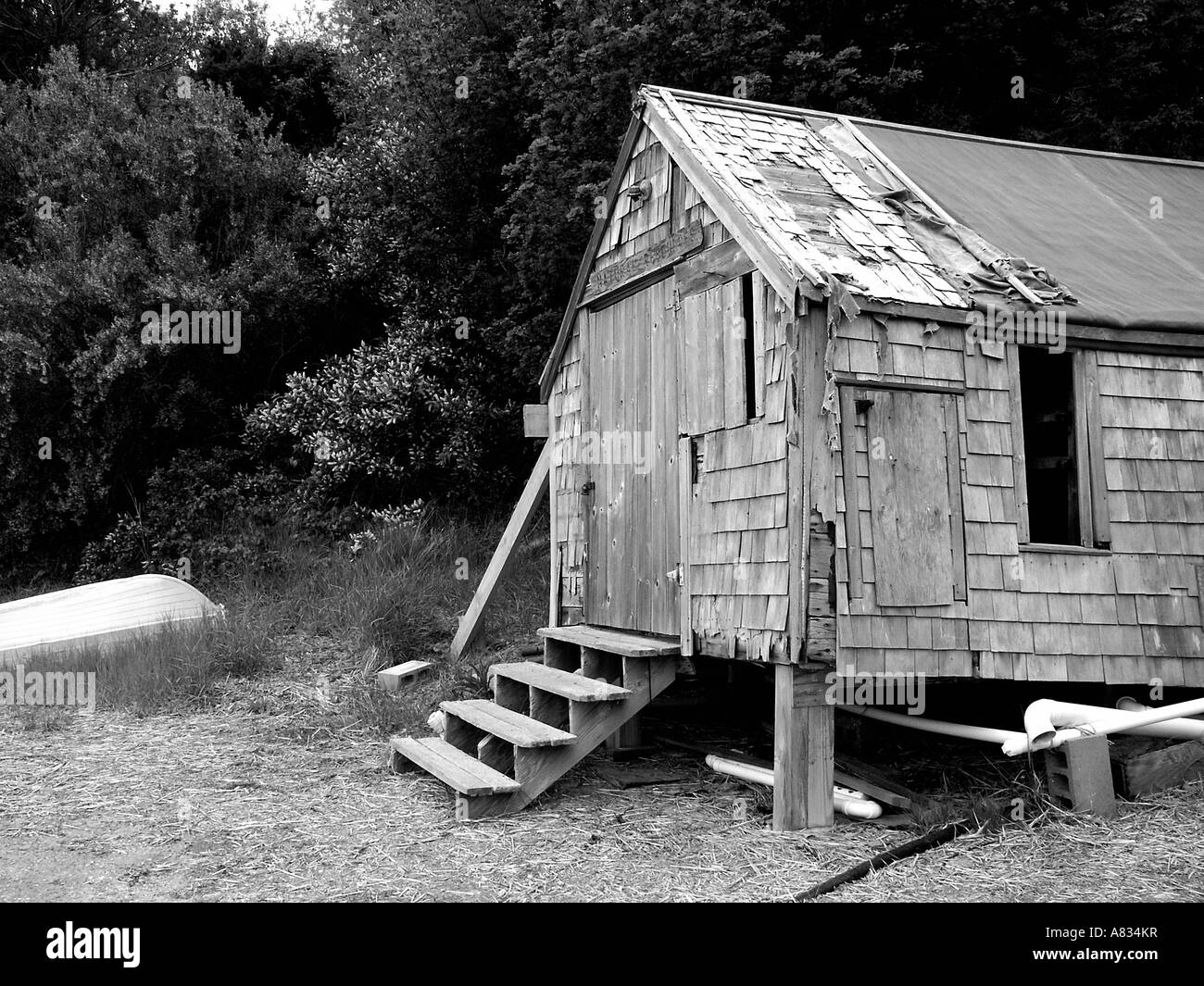 An abandoned-looking building on the shore of a pond on Cape Cod; full description below. - Stock Image
