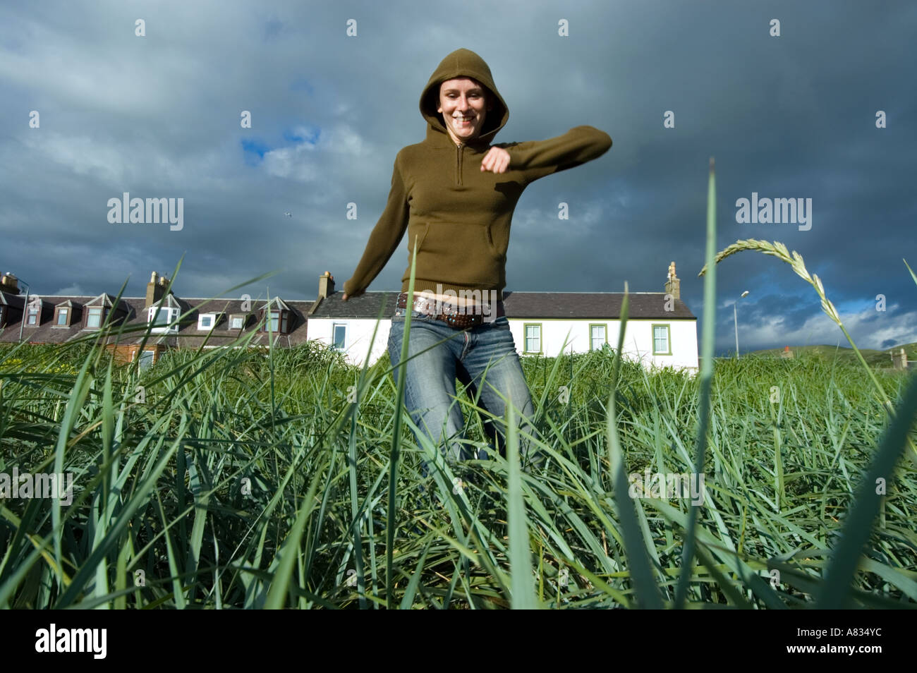 Young woman wearing jeans and t-shirt jumping merrily in tall grass - Stock Image