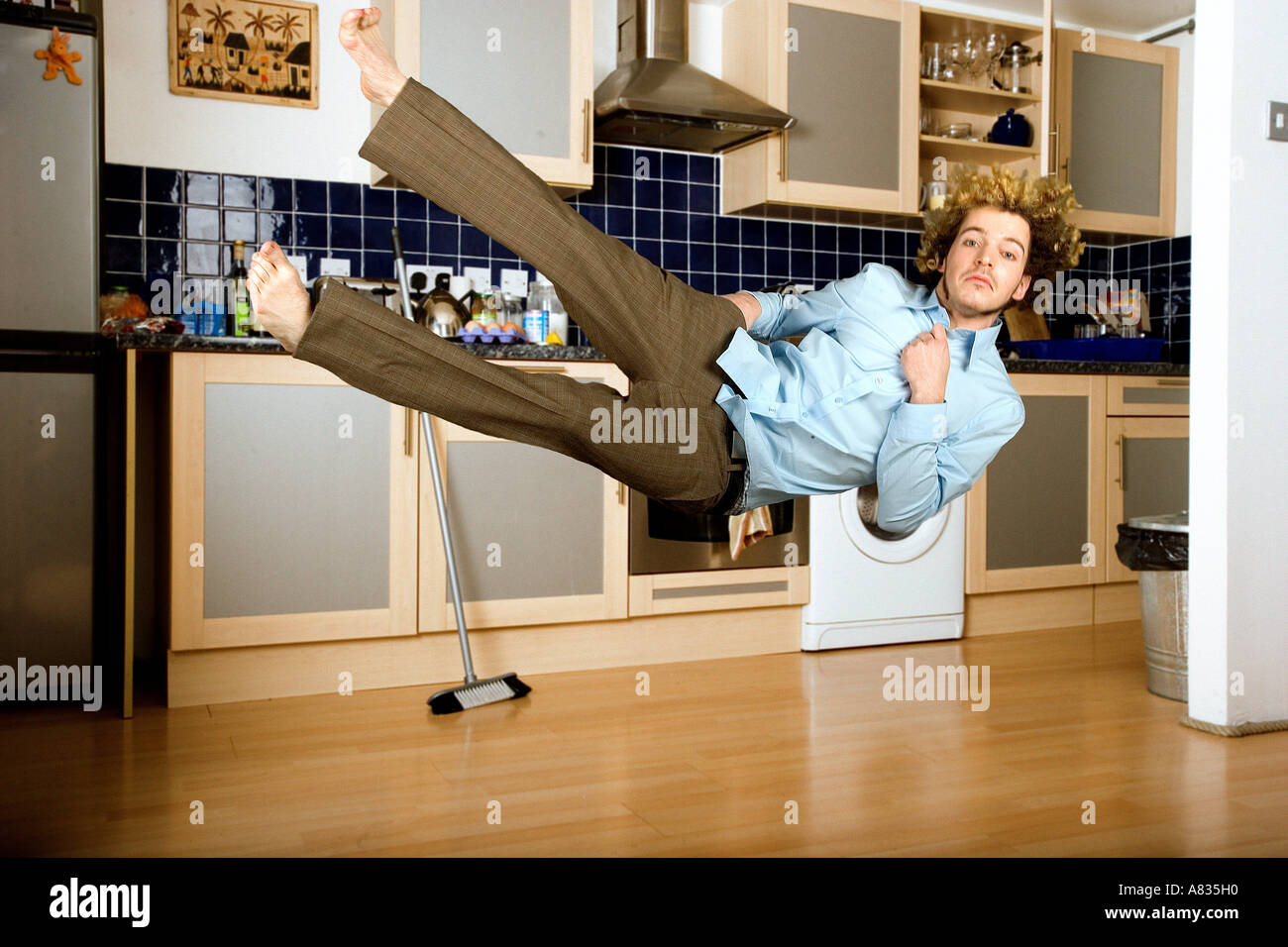 Airborne young man in pants and shirt in the kitchen falling ...
