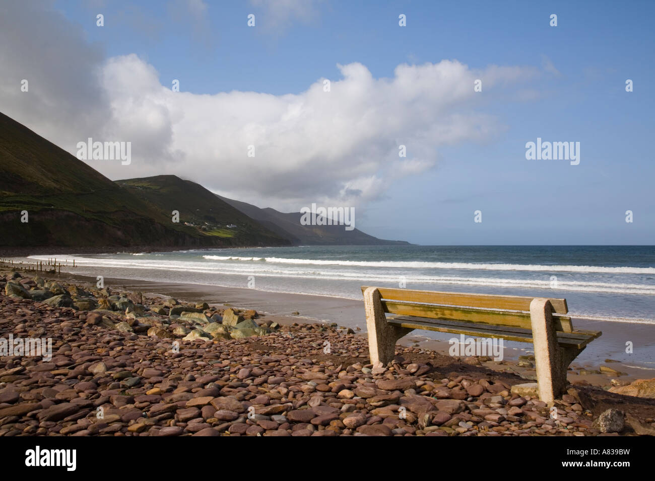 Empty bench seat overlooking long sandy empty beach of Ross Strand west of Ross Behy on Ring of Kerry Eire Southern - Stock Image