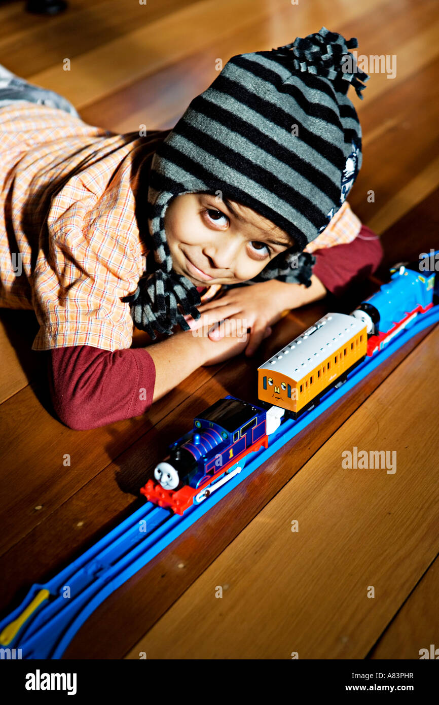Boy aged 5 years old wears hat and lies on polished wooden floor in sun with toy train set Stock Photo