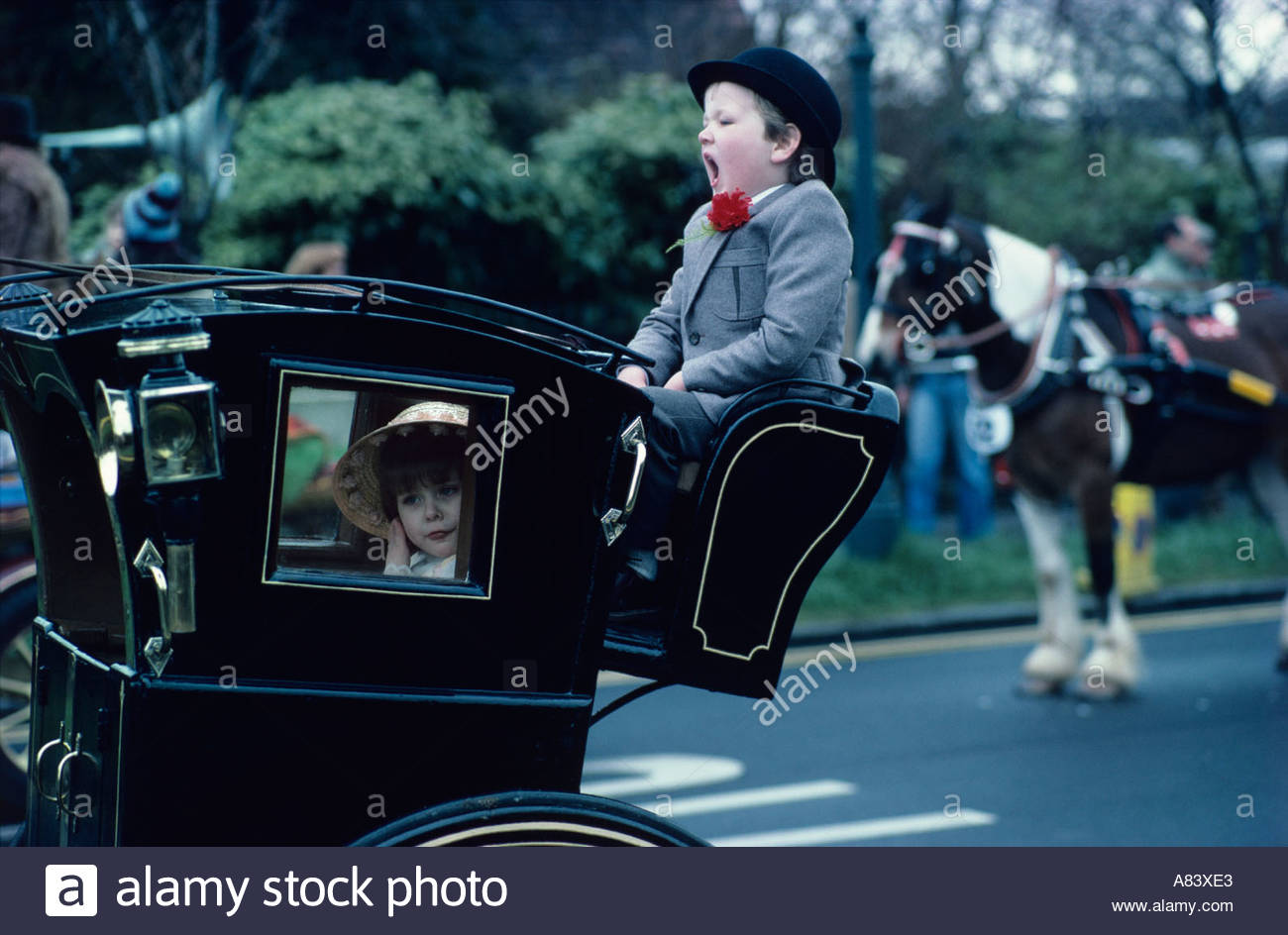 Yawning young footman and demure young passenger at the Harness Horse Parade in Regents Park London Stock Photo