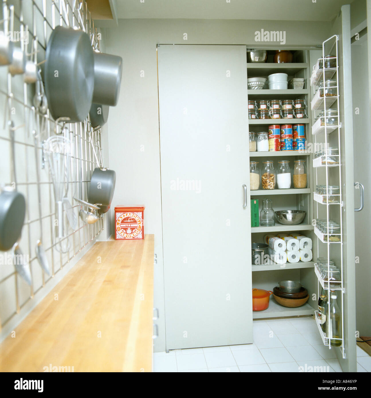 Open door to larder cupboard with shelves in galley kitchen with saucepans on metal rack & Open door to larder cupboard with shelves in galley kitchen with ...
